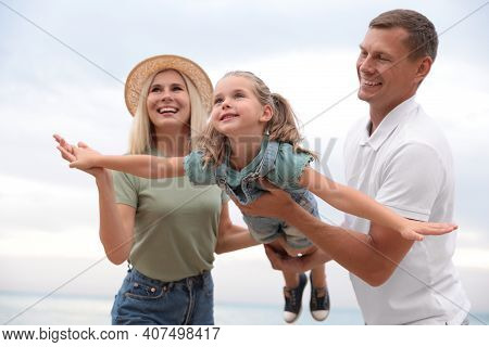 Happy Family Spending Time Together Near Sea On Sunny Summer Day