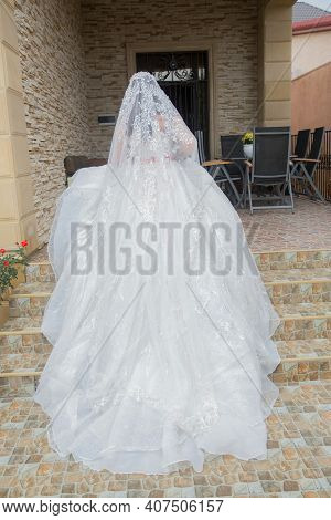 The Bride Takes A Photo Of The Wedding Dress From Behind At Home . The Bride In A Luxurious White Dr