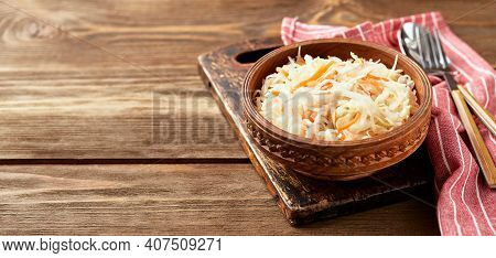 Sauerkraut, Fermented Cabbage With Carrots In Bowl On Wooden Background With Copy Space. Superfoods