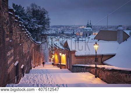 Cityscape Of Prague In Winter.  Lonely Man (in Blurred Motion) Walking On Staircase Against Lesser T
