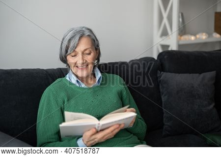 Happy Grandmother Senior Mature Woman In A Green Sweater, Sitting On The Couch And Reading A Book, M