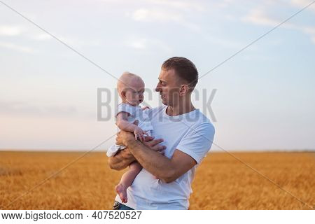 Young Father Tenderly Holding Baby On Wheat Field Background. Portrait Of Happy Father And Child.