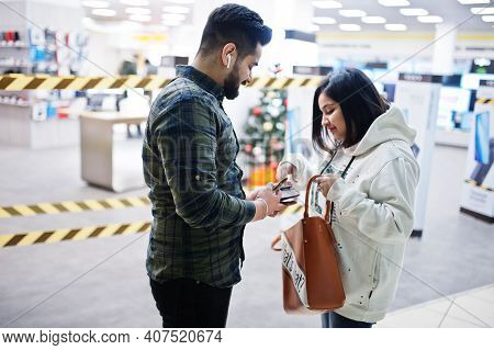 Indian Couple Take Money From Wallet At Trade Center.