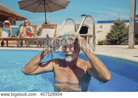 Group Of Senior Friends Relaxing And Sunbathing By The Swimming Pool, Enjoying Summer Vacation; Elde