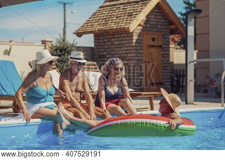 Group Of Senior People Relaxing And Sunbathing At The Swimming Pool On A Hot Sunny Summer Day, Sitti