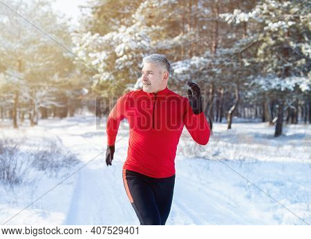 Cold Weather Running Concept. Fit Mature Man In Sports Clothes Jogging At Snowy Winter Park. Healthy