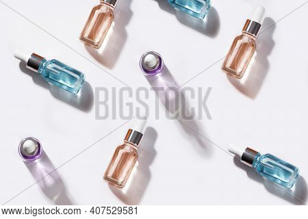 Bottle Of Cosmetic Product Oil Or Hyaluronic Acid On A White Background With Orange Slices, An Image
