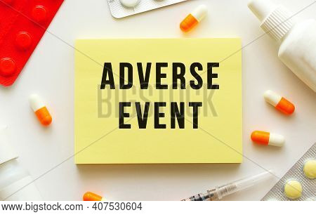 Notepad With Text Adverse Event On A White Background. Nearby Are Various Medicines.