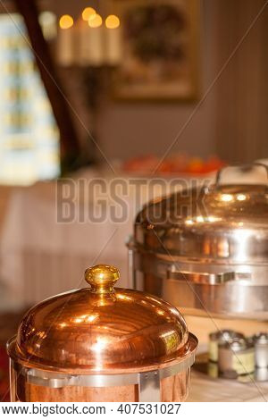 Old Copper Casserole With Lid And Brass Handles In Copper Flower Pot On A Normal Background. Food Ph