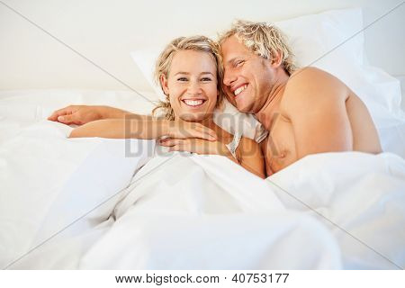 Happy young couple relaxing in bed