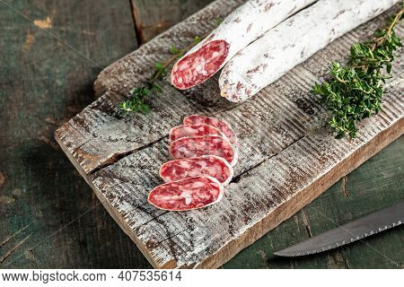 Spanish Fuet Salami Wurst With Thyme On A Wooden Cutting Board. Menu Recipe Place For Text, Top View