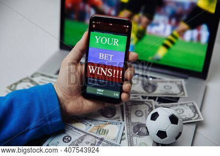 Lucky Winner At Football Betting With Phone In Hand And Dollar Bills. Betting And Gambling Concept