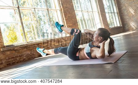 Fit Active Athletic Young Woman Doing Bicycle Crunch Situp Exercise Alone Lying On Mat Wooden Floor,