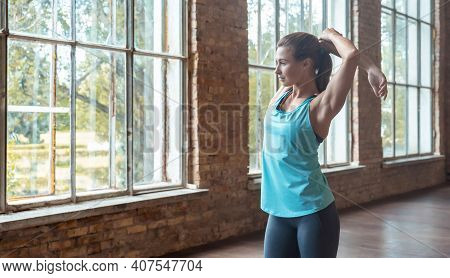 Sporty Fit Active Young Woman In Sportswear Warming Up Stretching Arms Stand Alone In Modern Studio