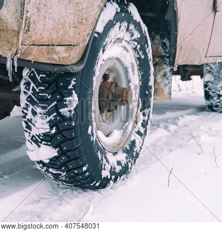 Studded Winter Car Tires On An Old Car On A Snowy Road