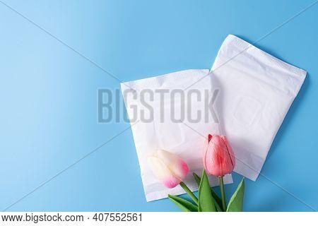 Sanitary Pad, Sanitary Napkin With Tulip Flower On Blue Background. Menstruation, Feminine Hygiene,