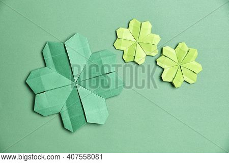 Origami Four-leaf Shamrocks, Made Of Green Paper, On Green Background. Concepts Of Luck And St. Patr