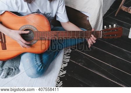 Playing The Guitar In Close-up. The Girl Is Holding A Guitar. Wooden Guitar In Hand.