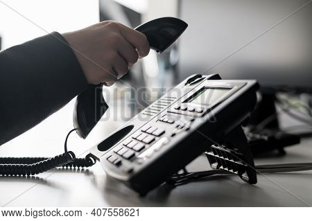 Close-up Of The Hand Of A Female Office Worker Dialing A Number On A Landline Phone. Faceless Woman