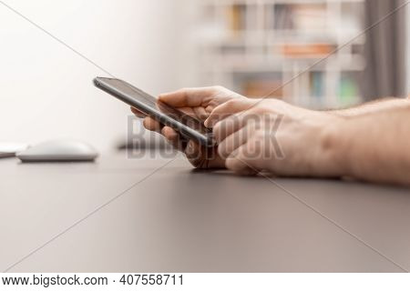 Close Up View Of Hand With Mobile Phone. Work With The Cell Phone. Working From Home, Home Office