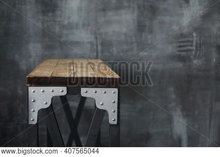 Wooden Table With Metal Inserts. Loft Style Table On The Background Of A Dark Wall In Grunge And Lof
