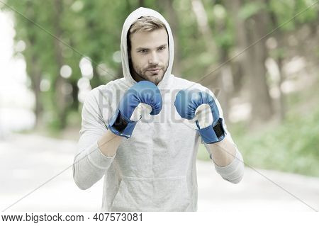 Training For Big Day. Man Athlete On Concentrated Face With Sport Gloves Practicing Boxing Punch, Na