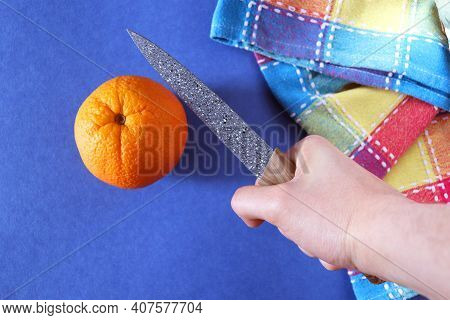 Orange, Checkered Dishcloth And Ceramic Knife. Ceramic Knife In A Hand Over An Orange