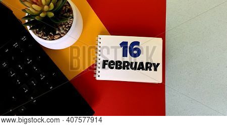 February 16 On A Multicolored Background On A White Notebook.next To It Is An Artificial Flower In A