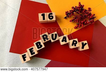 February 16 On A Multi-colored Background On Wooden Cubes.near Artificial Red Berries .winter.calend