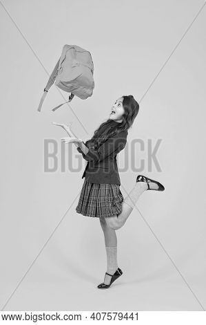 Happy Little Child Girl In Formal Uniform Throw School Bag Up Yellow Background, Holidays.
