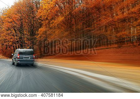 Car Is Driving Along The Road Against The Background Of The Autumn Forest. Blur Effect.
