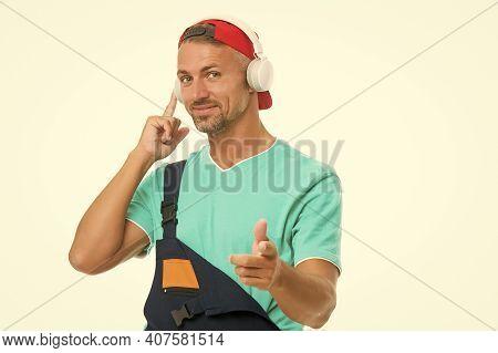 Headphones Protecting Ears. Workman Wear Headphones Pointing Finger. Worker Listen To Music In Headp