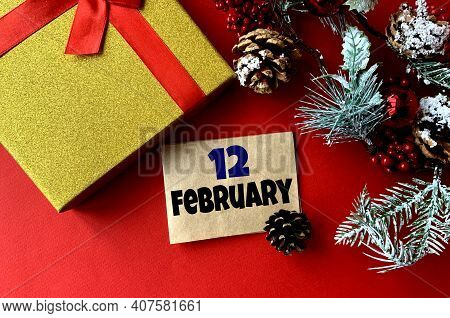 February 12 On Craft Paper. Near Fir Branches, Cones, Ribbon,gift Box On A Red Background.calendar F