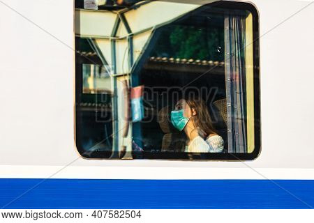Young Woman Wearing Surgical Face Mask Protect Against Coronavirus Infection At Public Train Station