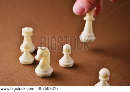 White Pieces Of Chess Game On A Brown Table Without A Playing Field. The Hand Holds One Figure. Play