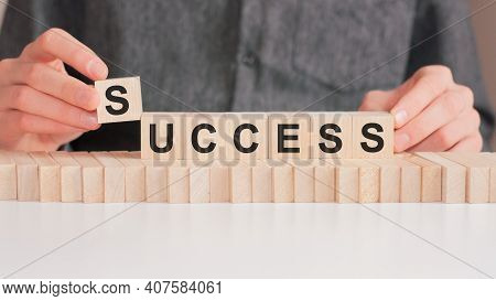The Hand Puts A Wooden Cube With The Letter S From The Word Success. The Word Is Written On Wooden C