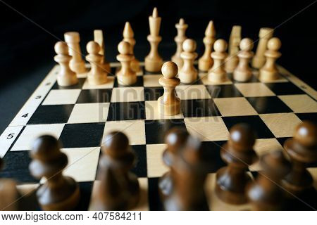 Close Up Of White And Black Chess Pieces On Board. Selective Focus On First Move Of White Pawn On Ch