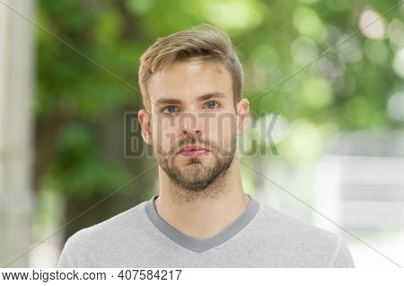 Man With Bristle On Calm Face, Nature Background, Defocused. Man With Beard Or Unshaven Guy Looks Ha