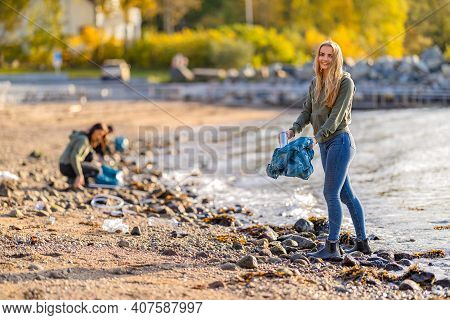 Dedicated Smiling Young Volunteers Cleaning Beach For Plastic On Sunny Day