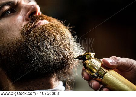 Bearded Man In Barbershop. Man Visiting Hairstylist In Barbershop. Barber Works With A Beard Clipper