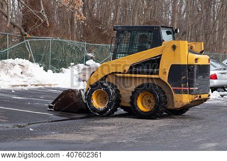 A Yellow Snow Grader Cleans Snow-covered Roads On A City Street Cold