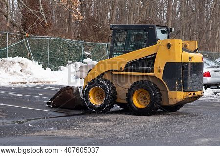 A Yellow Snow Grader Cleans Snow Covered Roads On A City Street Cold Work