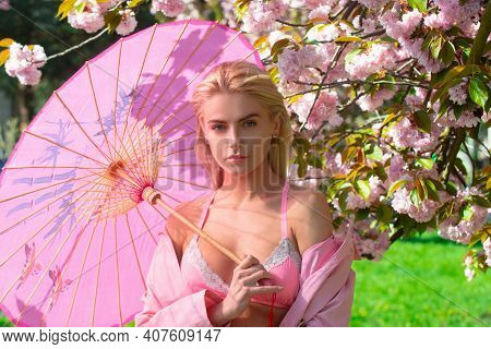 Outdoor Portrait Of Young Beautiful Fashionable Woman Posing Near Japanese Blossom Sakura Tree. Spri
