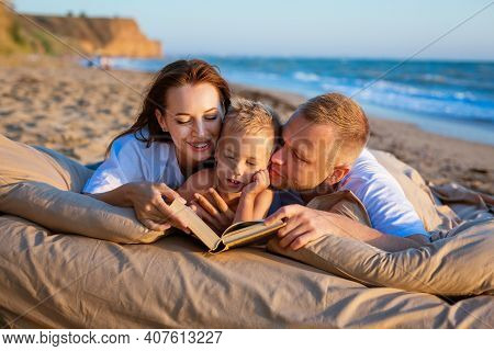 A Young Couple, Dressed In Light-colored Clothes, Lies With A Child On The Seashore And Read A Book.