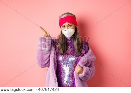Covid And Fashion Concept. Fashionable Asian Mature Woman In Face Mask And Disco Dress Pointing Fing