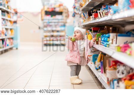 Shopping. A Cute Baby Girl Stands At The Supermarket Shelves With A Pear In His Hand. The Concept Of