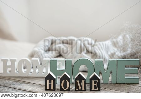 Still Life With The Words Home For Home Decor On Blurred Background. The Concept Of Home Coziness An
