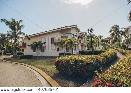 Beautiful Backyard With A Garden In Front Of A Two-story House. Tropical Luxury House With Palm Tree