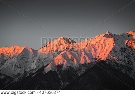 Beautiful Sunset In The Winter Mountains. Purple Snow-covered Peaks In The Evening Sunlight. Caucasu