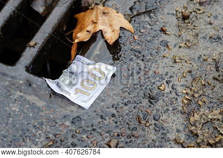 Money. American One Hundred Dollar Bill On The Edge Of A Storm Drains Grate After Rain. Wet Banknote
